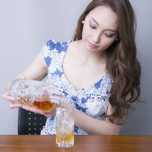 グラスに飲み物を注ぐ女性