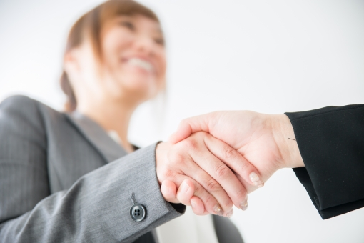 握手をするスーツの女性